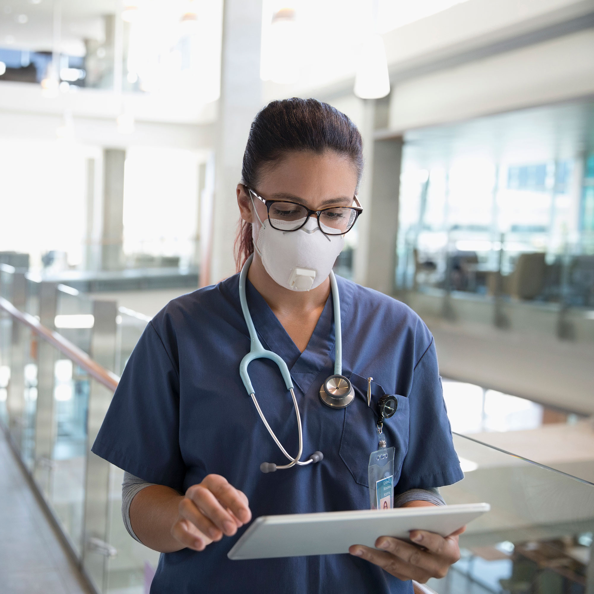 A nurse, wearing a scrubs and a stethoscope, stands in a walkway to user her tablet.