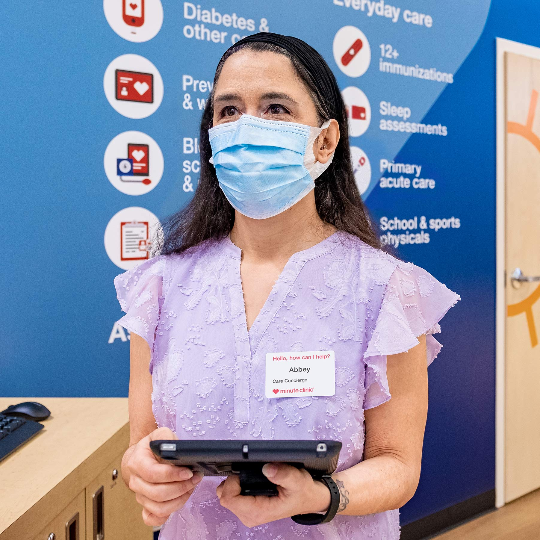 A HealthHUB concierge seen at a CVS Pharmacy location, wearing a face mask and using a tablet computer.