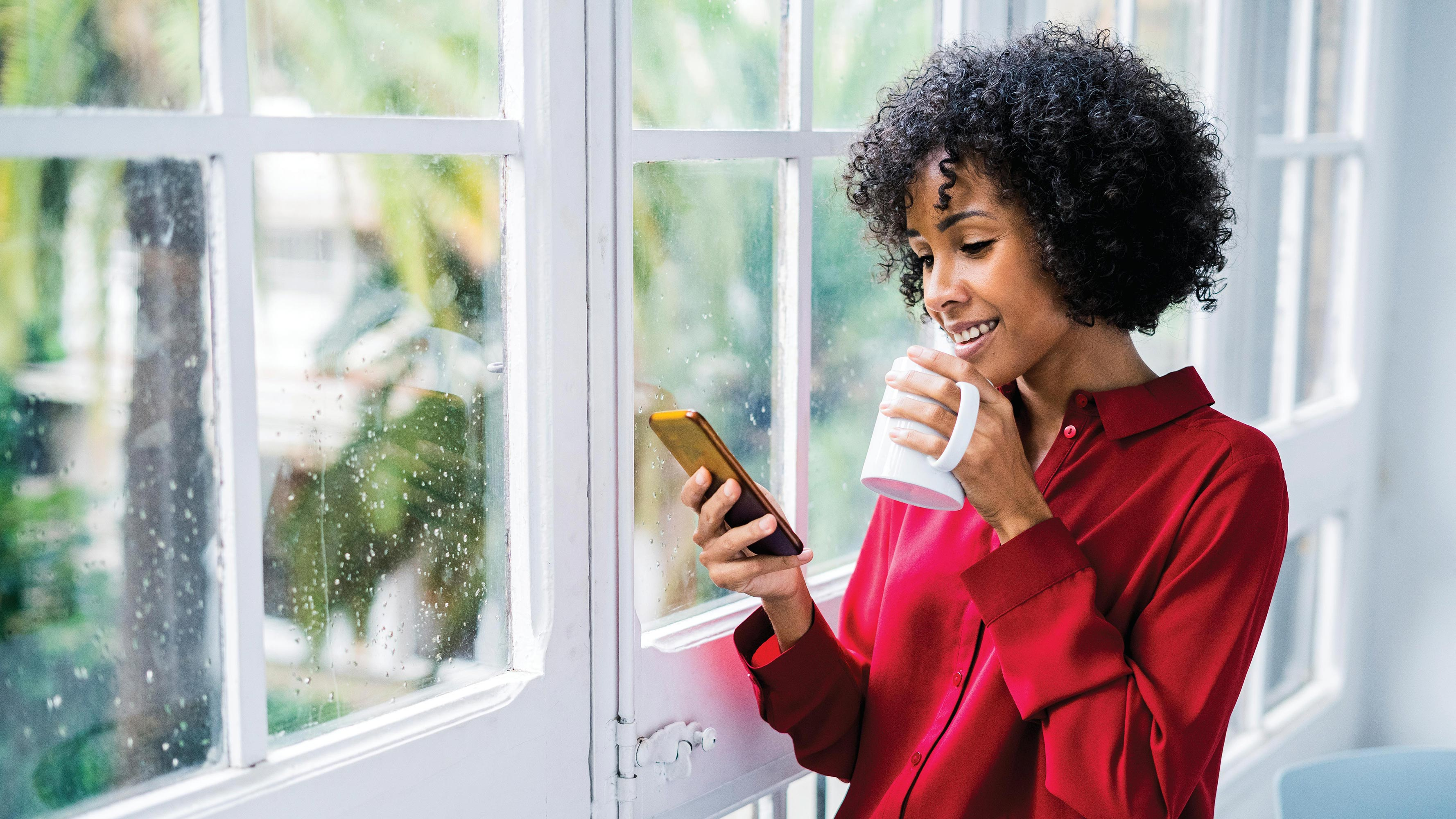 A young woman with curly hair, wearing a red button-down, collared shirt, stands by her window to drink coffee and scroll through her phone.