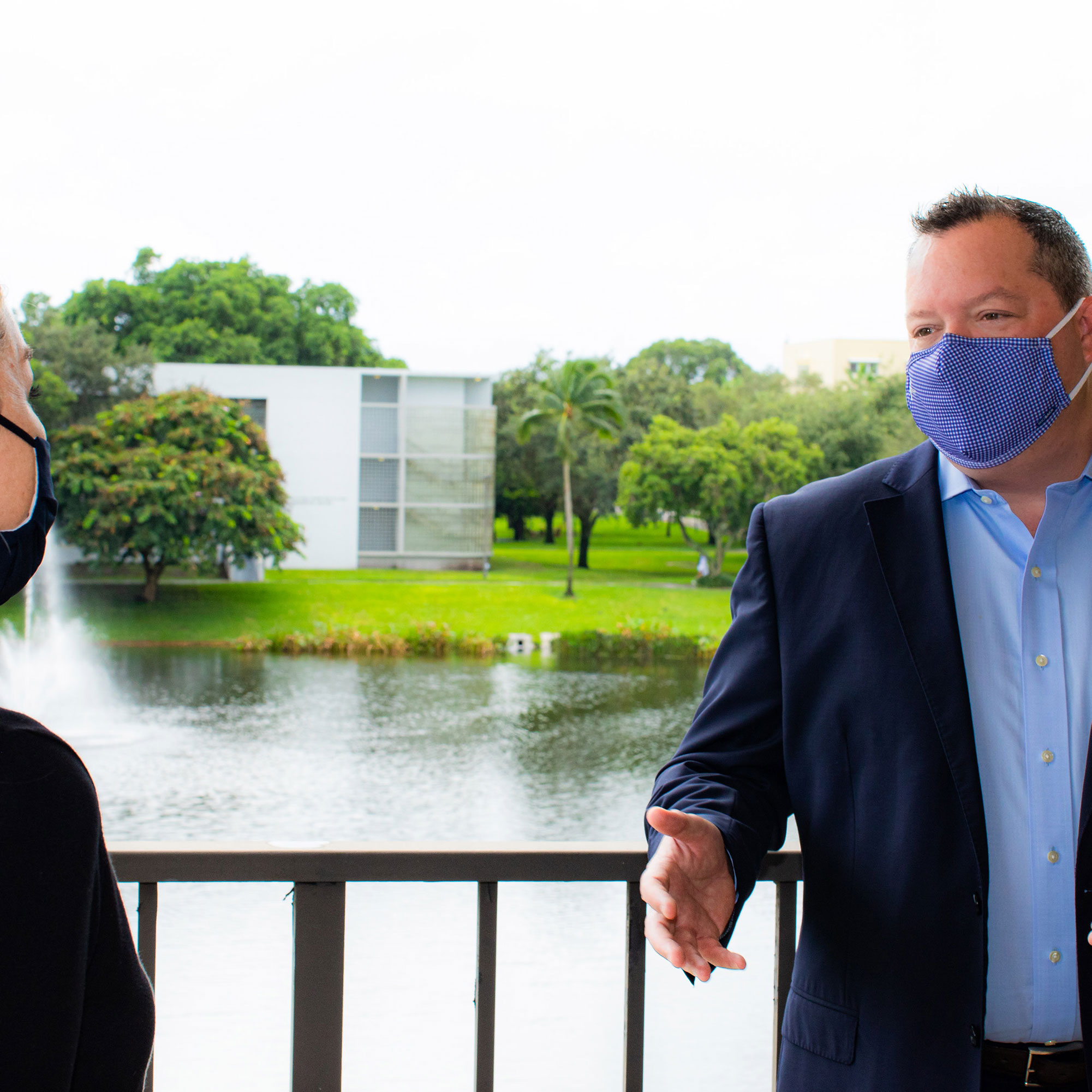 Lynn University Chief Strategy and Technology Officer Christian Boniforti wearing a mask in conversation with a woman wearing a mask and social distancing.
