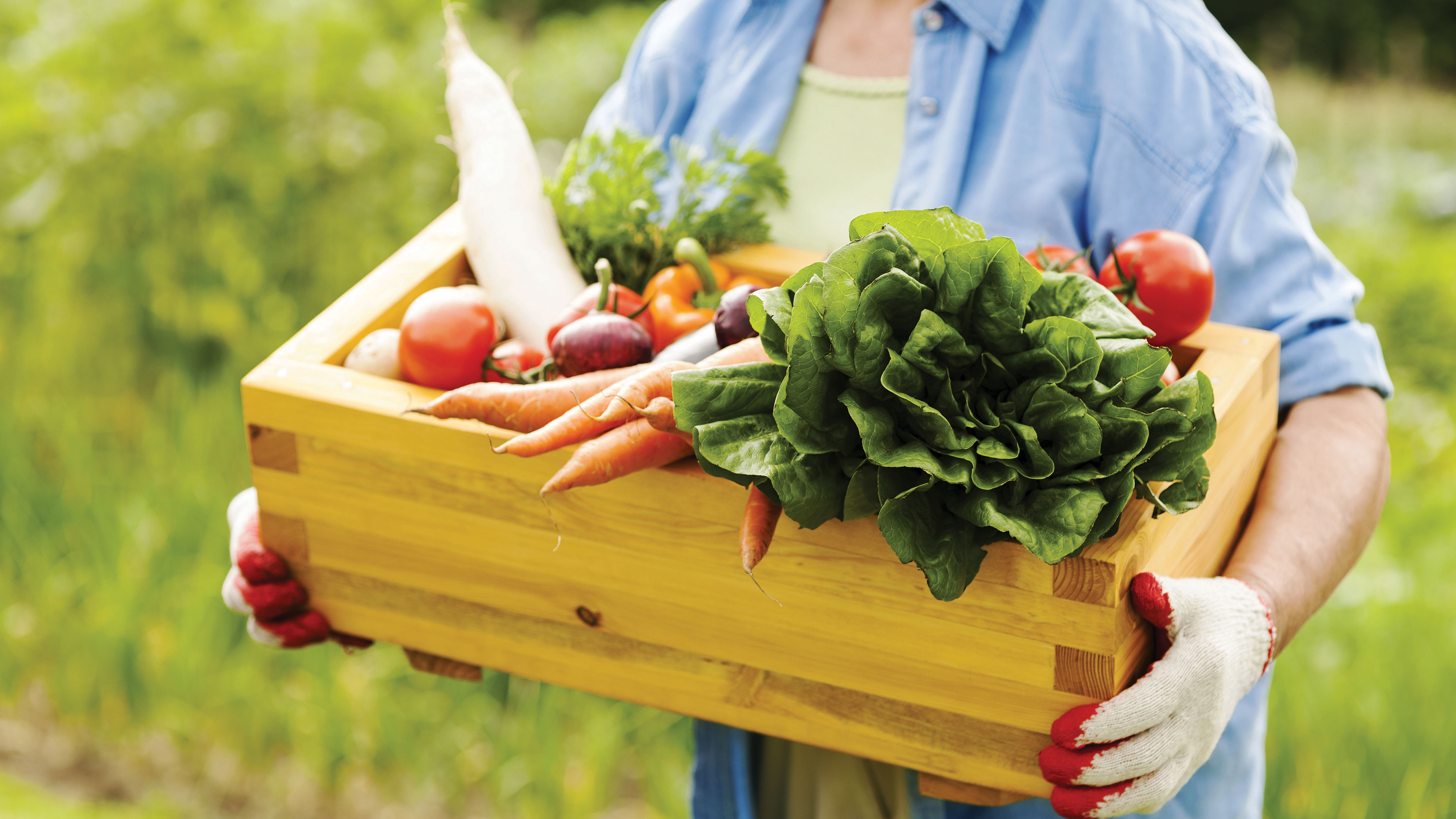 Woman holding a wooden basket of fresh produce filled to the top.