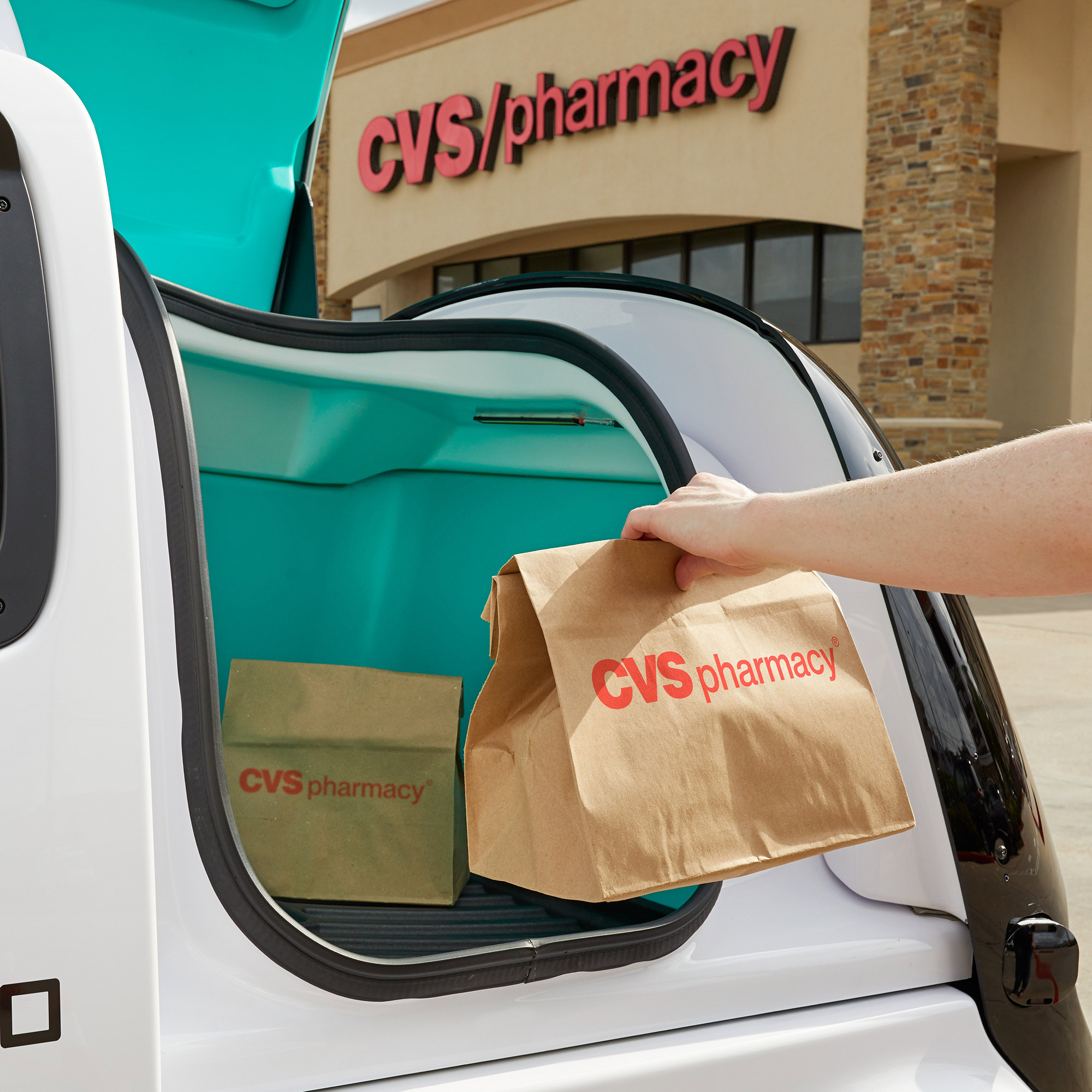 A CVS Pharmacy customer collects a delivery from a Nuro autonomous vehicle outside of a CVS Pharmacy location in Texas.