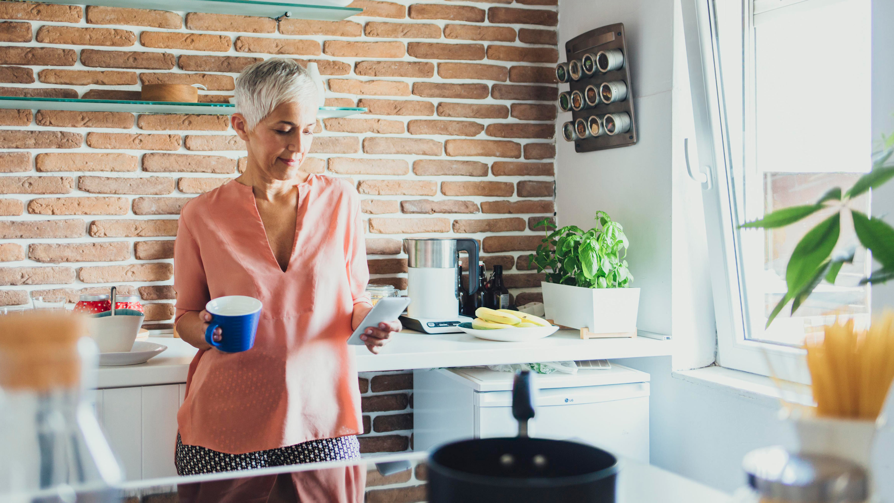 An older female, wearing bright and comfortable clothing, stands in a very modern kitchen with a prominent brick wall, holding a mug in her right hand while using her mobile phone with her left hand.