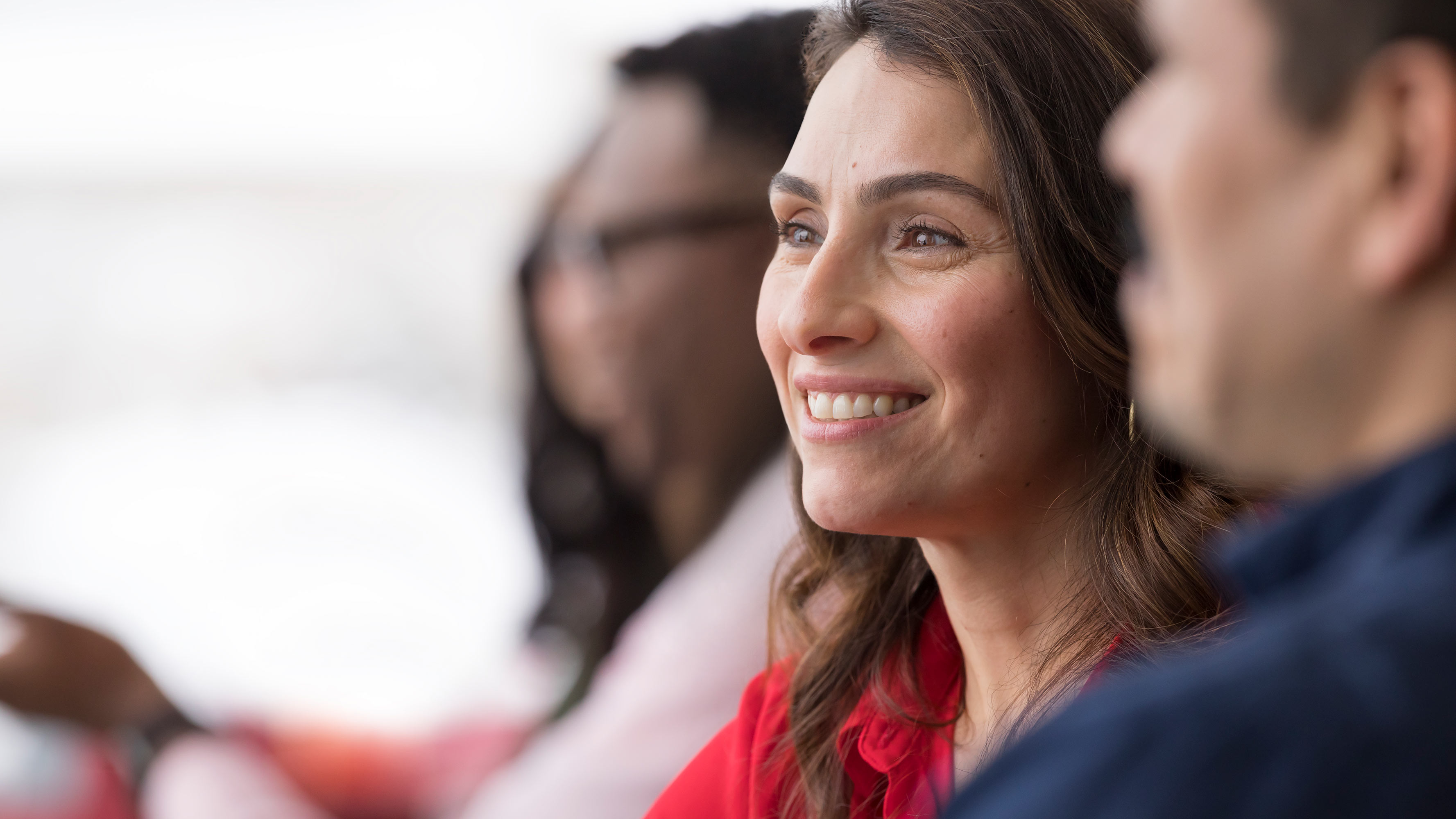 A close-up photo shows a female CVS Health employee smiling while sitting around a conference table at the company's Woonsocket, Rhode Island headquarters.
