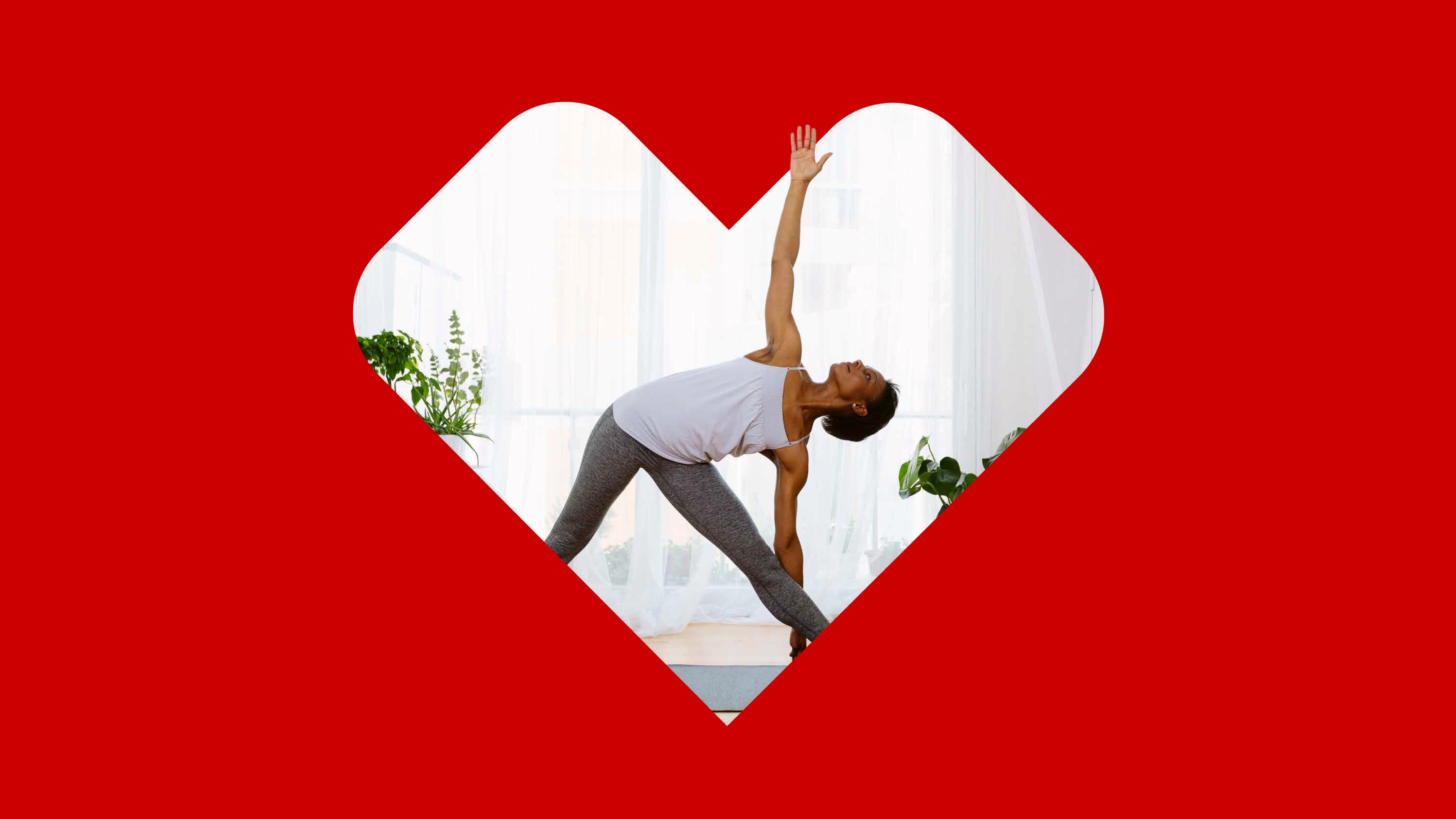A woman in gray athletic clothes stretches and practices yoga poses in a very light and bright room. The photo is set inside of a CVS Health® heart on a red background.