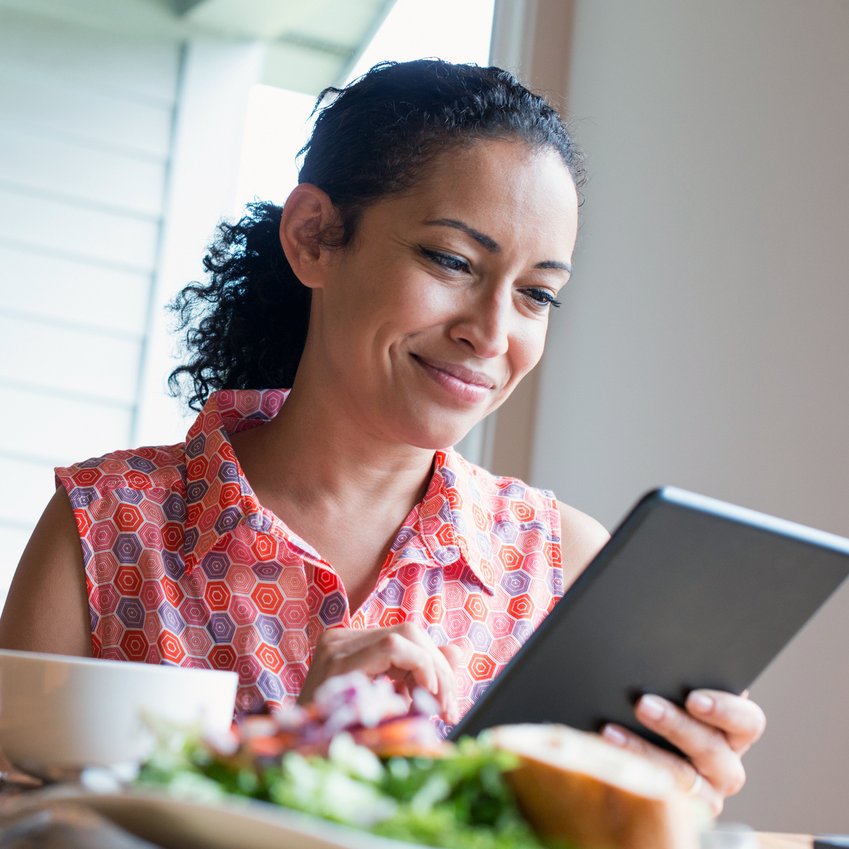 A woman sits at a dining room table eating a salad and a piece of bread while quietly smiling and reading a tablet computer.