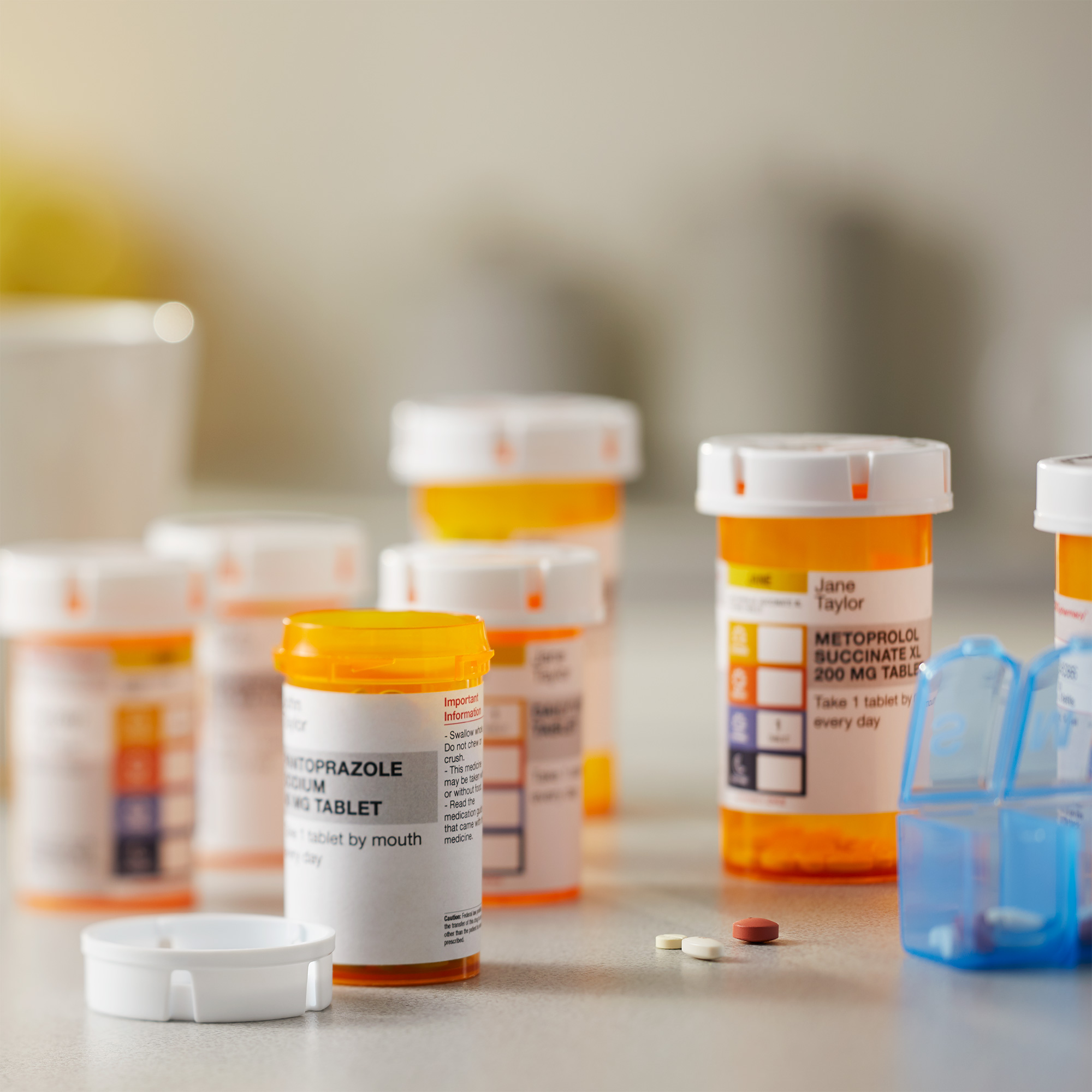 Prescription bottles on a table near a pill organizer.
