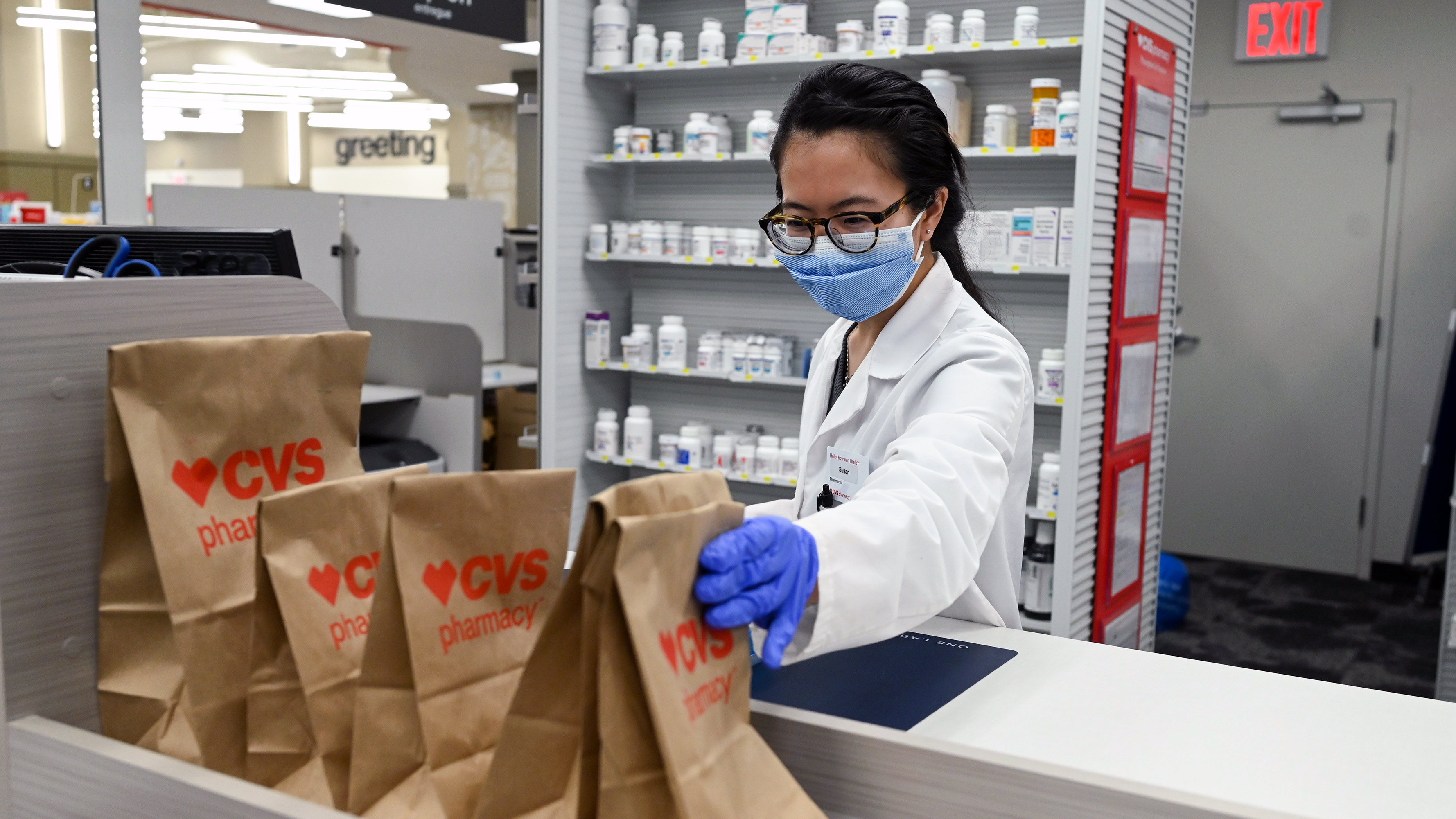 A CVS pharmacist prepares prescriptions while wearing personal protective equipment (PPE).