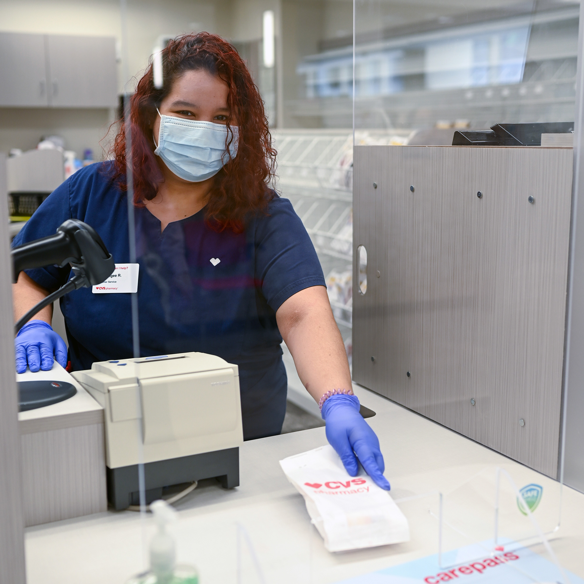 A CVS Pharmacy technician prepares prescriptions while wearing personal protective equipment (PPE) behind a plexiglass screen.