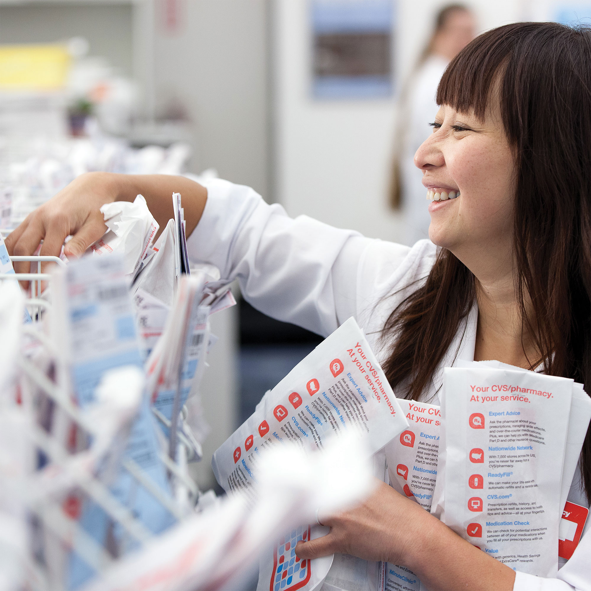 A CVS pharmacist smiles while she files through prescriptions behind the pharmacy counter.