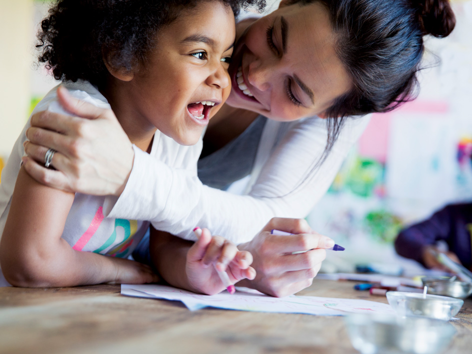 A mother and child enjoying a coloring book activity.