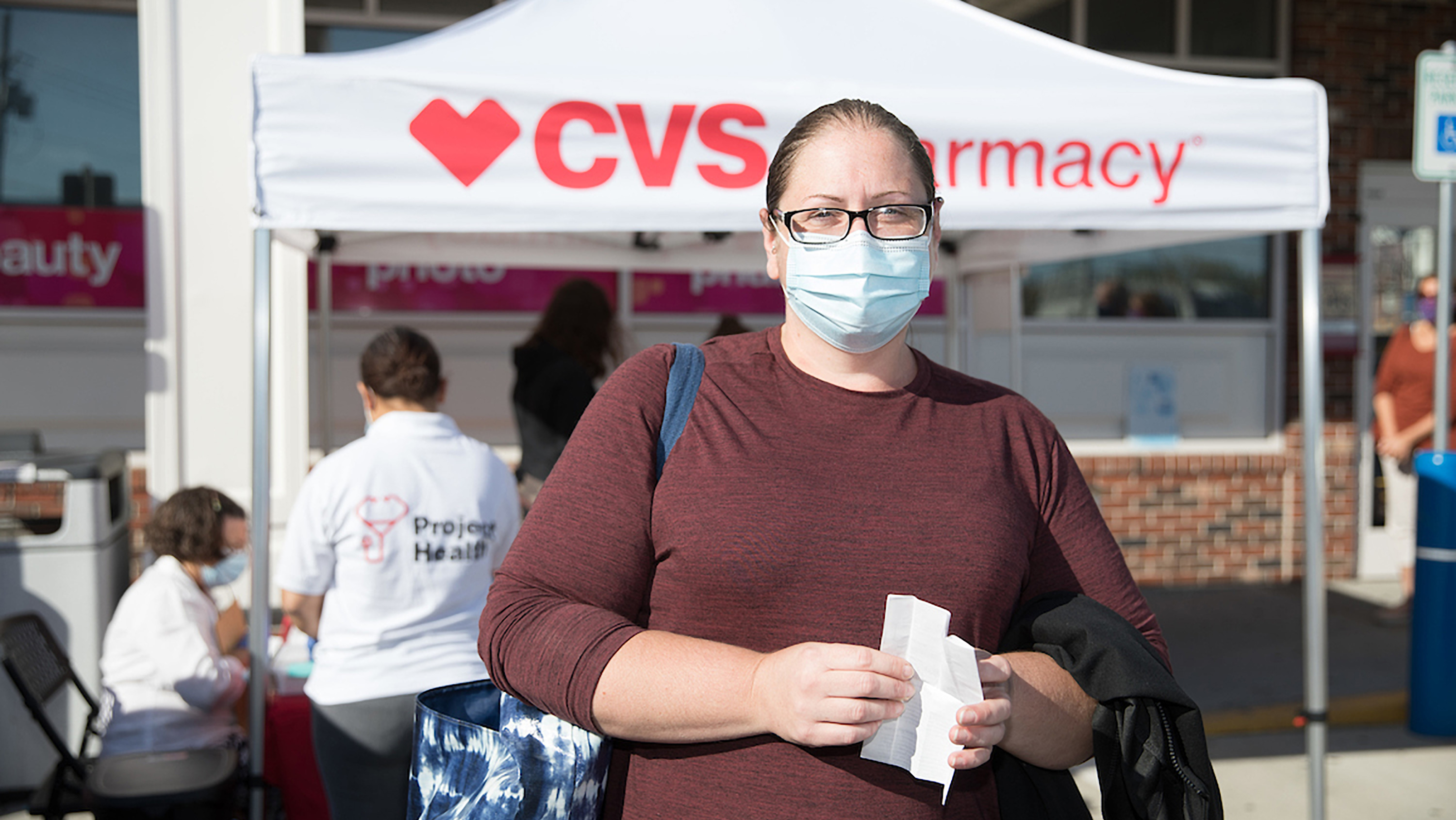 A female customer standing at a Project Health booth located in the parking lot of her local CVS Pharmacy.