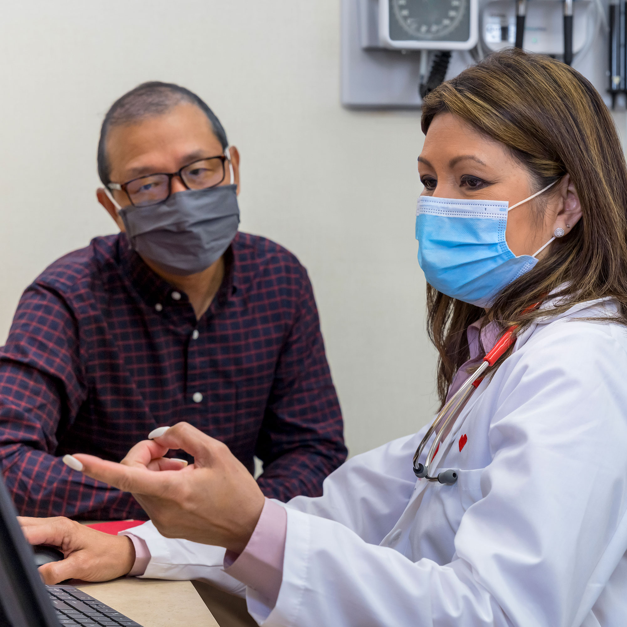 A physician reviews a patient's information with them.