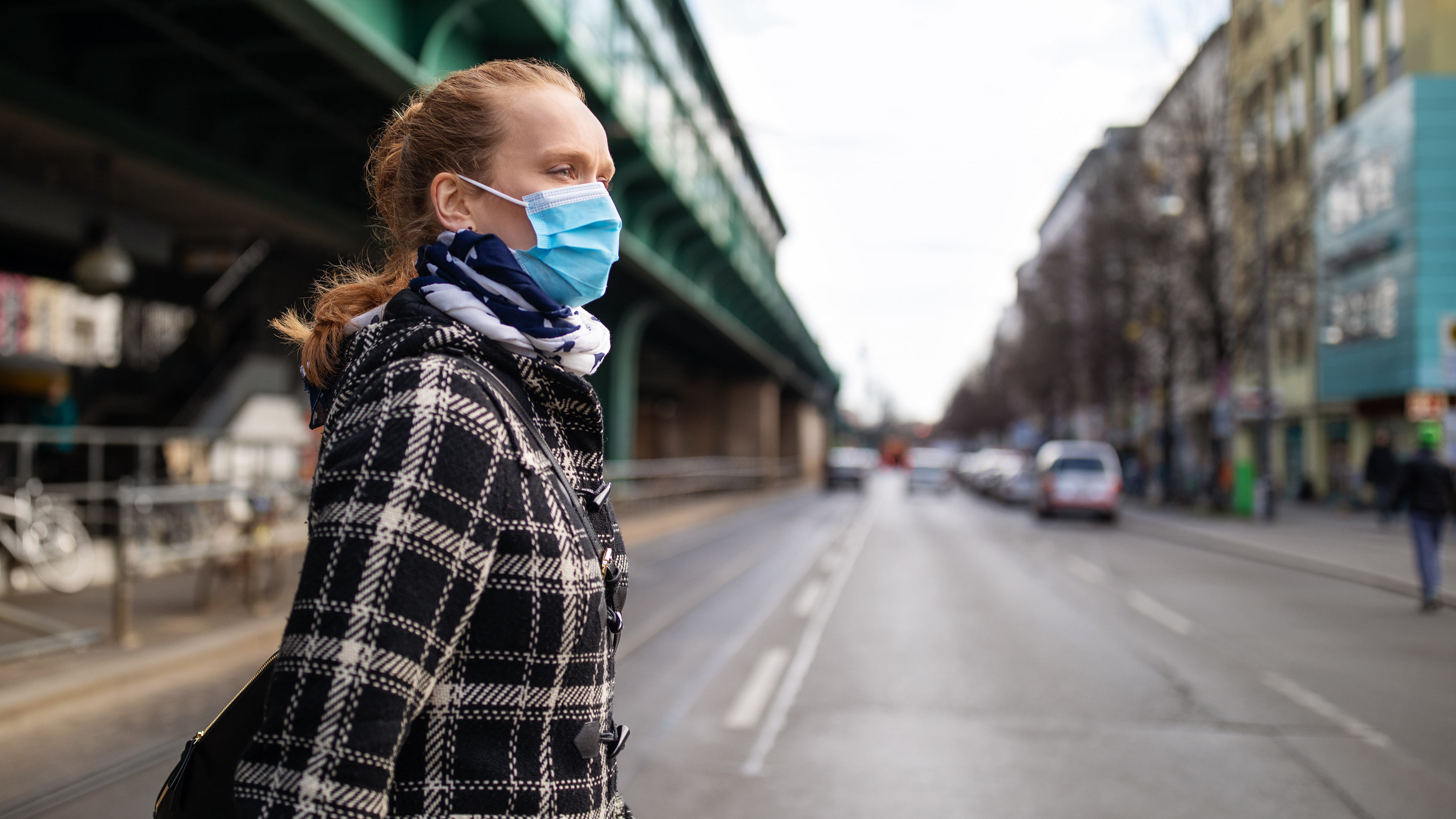 A woman, wearing a face mask, walks across a city street during her commute.