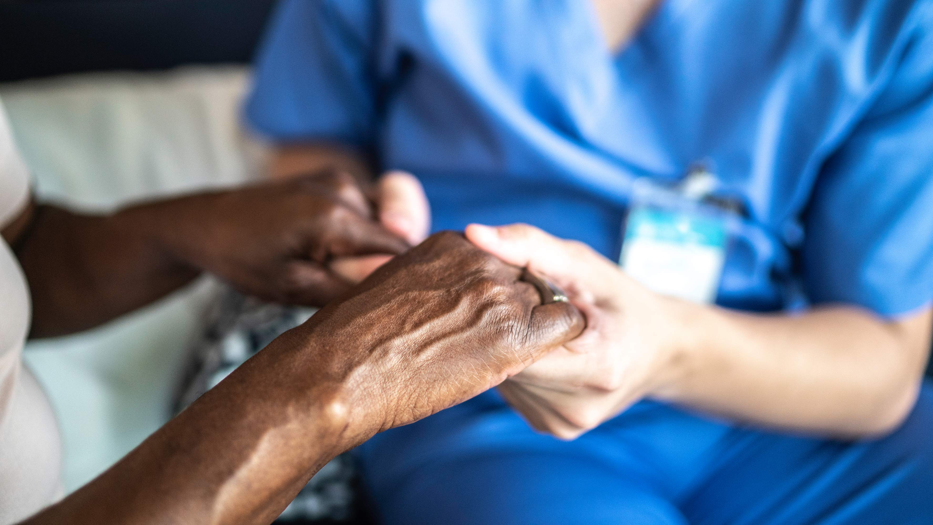 A close-up photo of a nurse, wearing bright blue scrubs, holding the hand of patient.