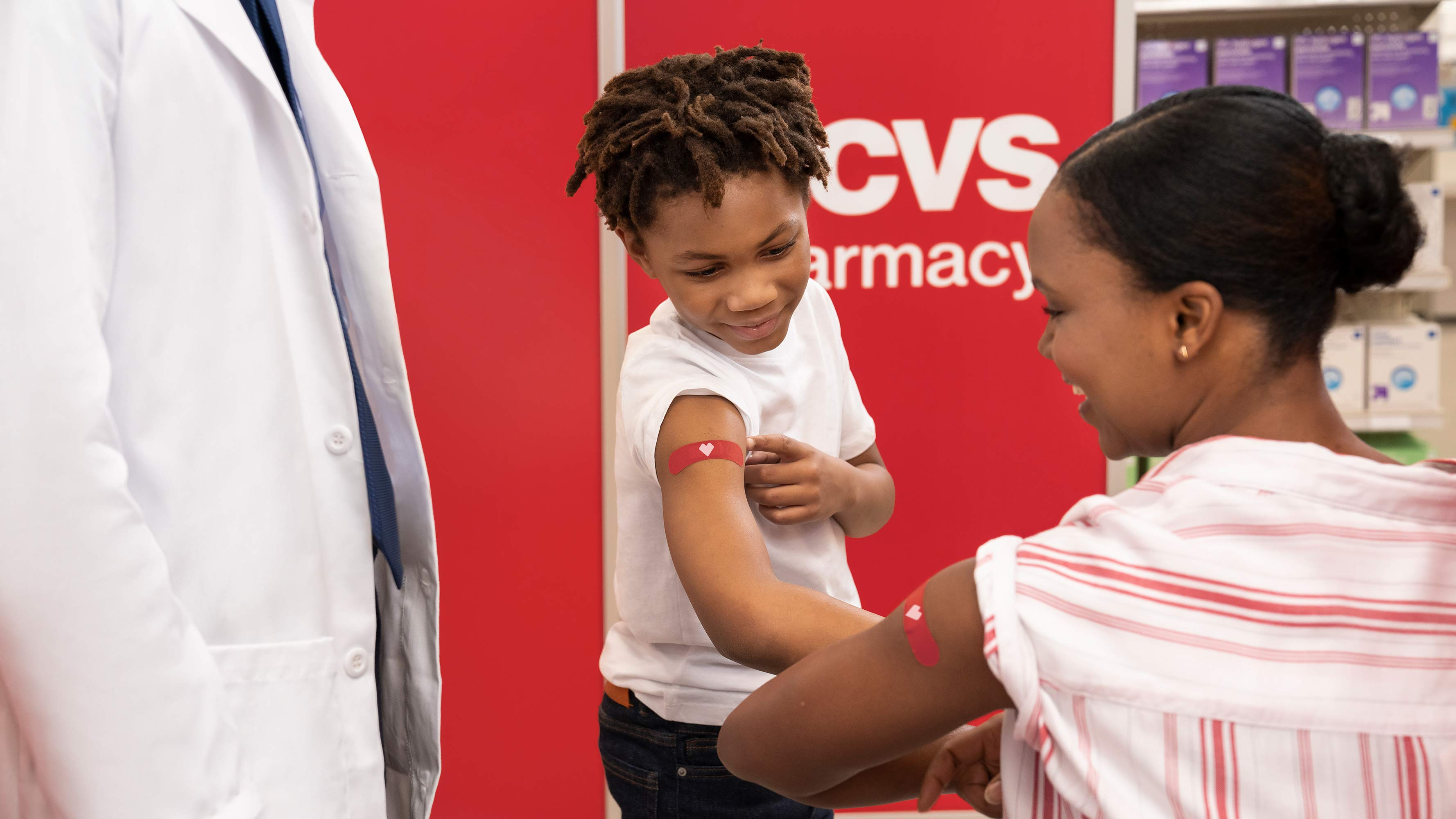 A young boy shows his upper arm bandaid to an adult with a matching bandaid.