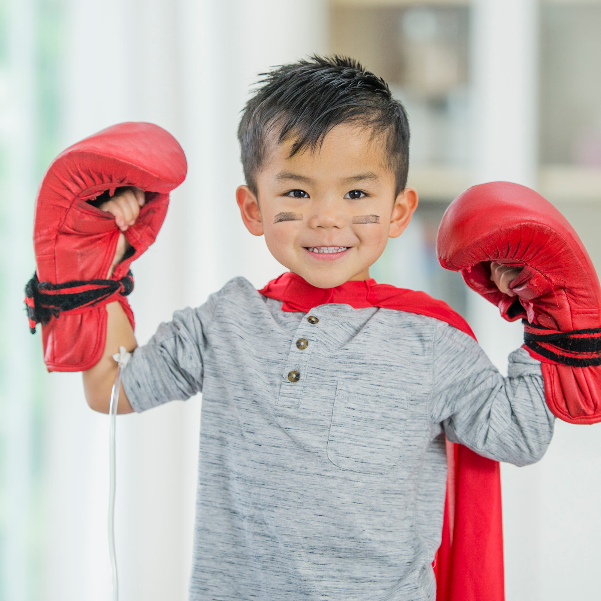 A young boy smiles while receiving an infusion treatment while wearing boxing gloves, a cape, and face paint.