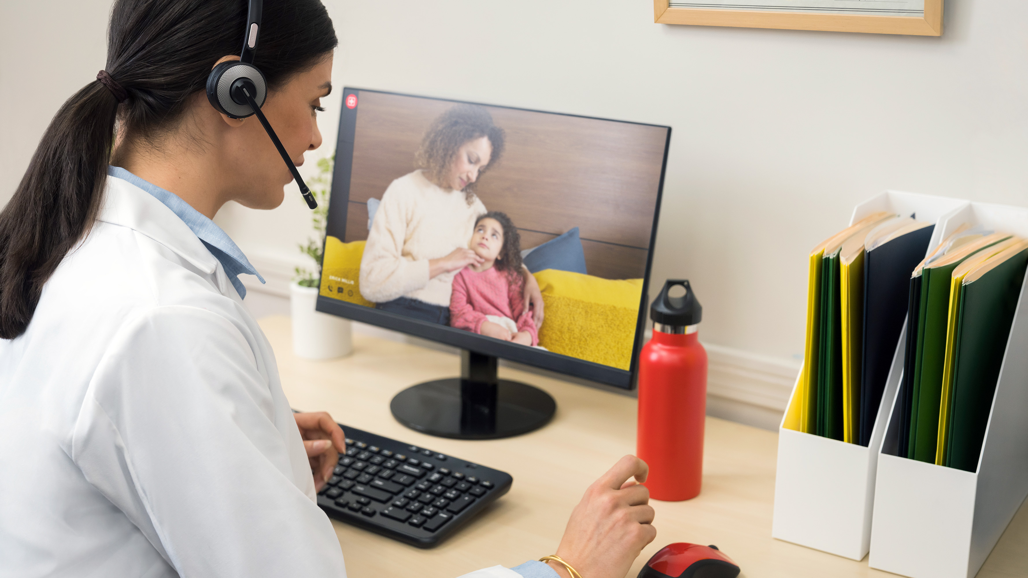 A practitioner consults a female adult patient with a child via video call during a telemedicine visit.