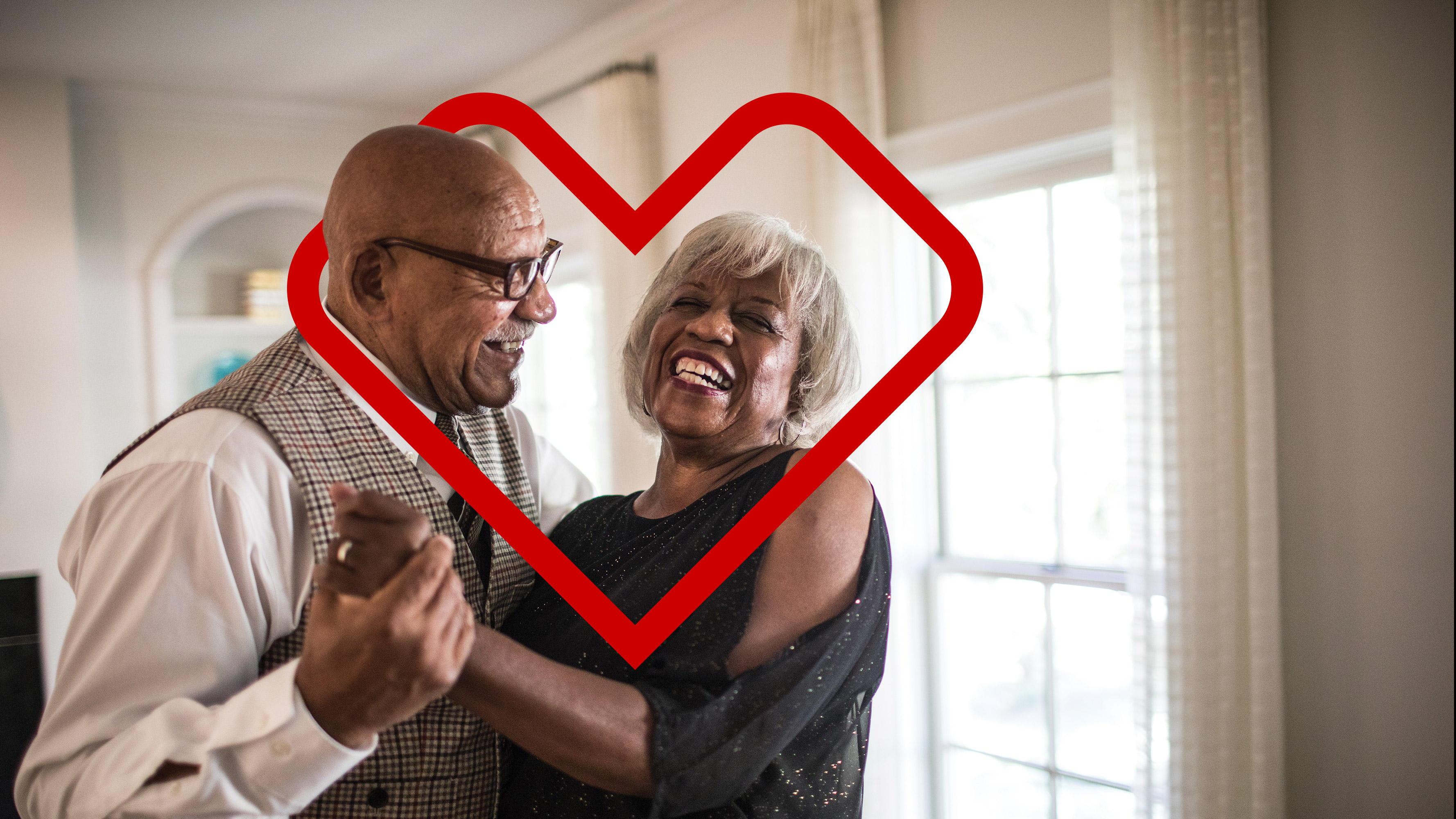 A  photo of an older African-American couple dancing in their living room, smiling. The older female is enclosed in a red CVS Health® heart outline.