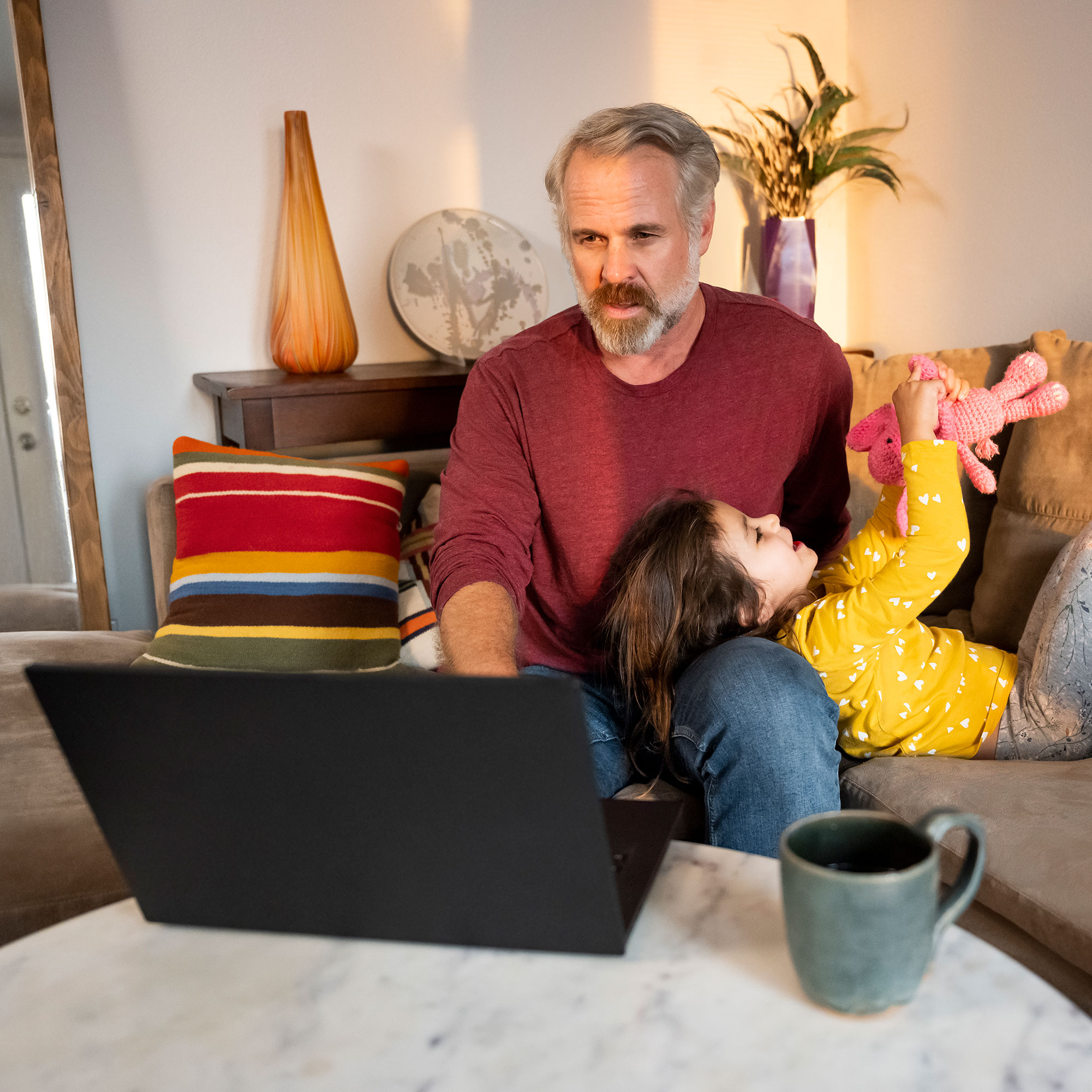 Parent uses laptop to engage in virtual care while cuddling their child on the couch.
