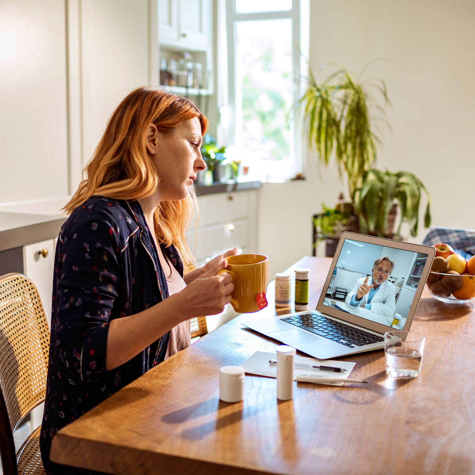 A woman sits at her kitchen table to have a cup of coffee while she has a virtual appointment on her laptop.