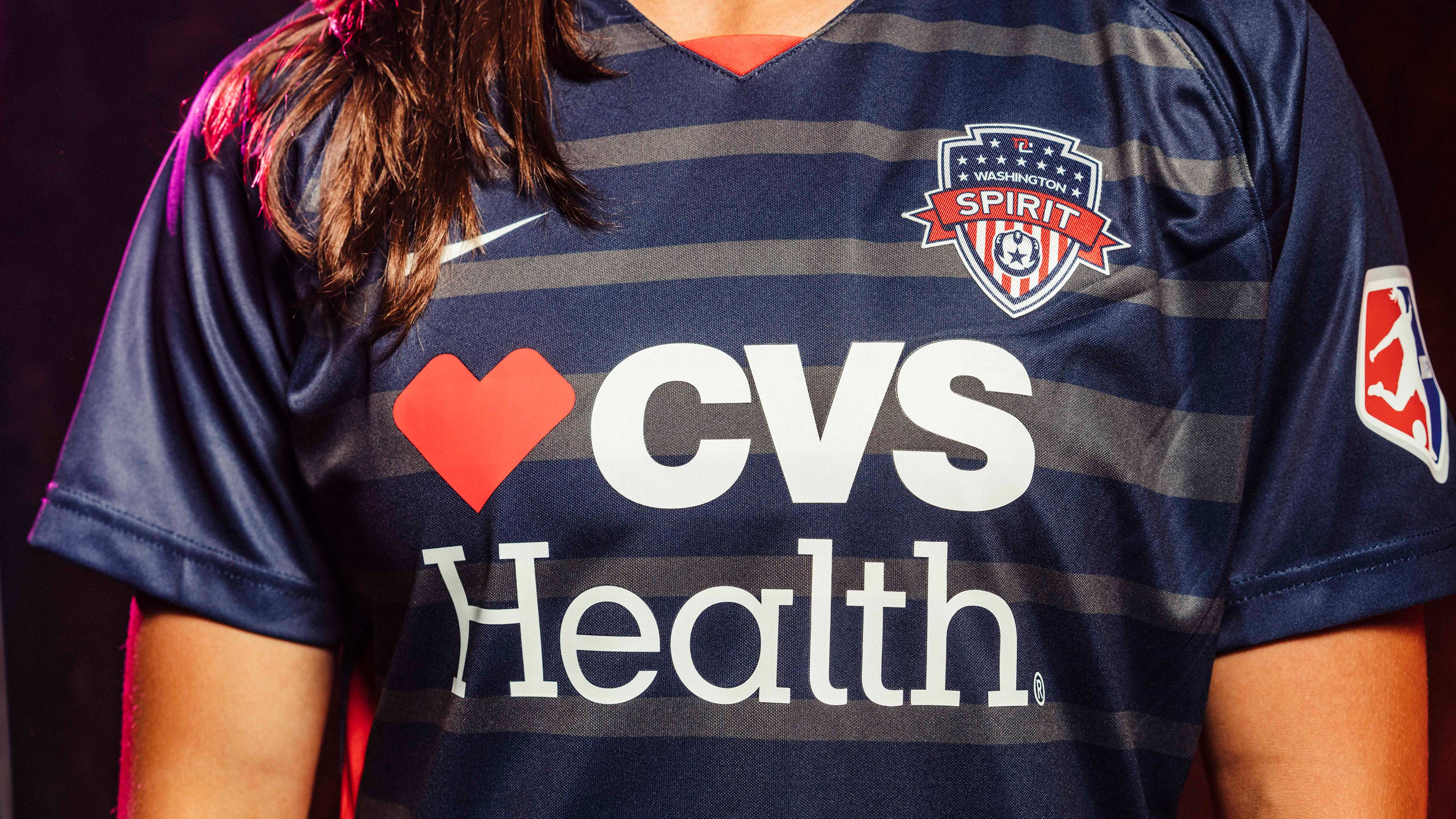 A close up photo of the Washington Spirit (professional soccer team) uniforms, which are dark navy blue and feature CVS Health's logo on the front under the soccer team's branding.