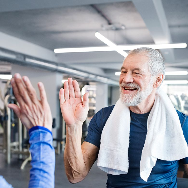 A photo of an older gentleman completing a workout at a gym, wearing a towel around his neck while high-fiving a fellow gym member.