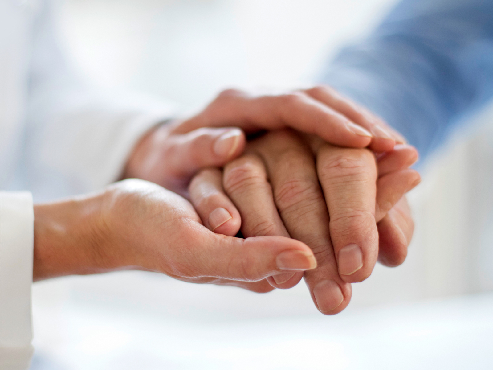 Close-up photograph of doctor holding patient's hand.