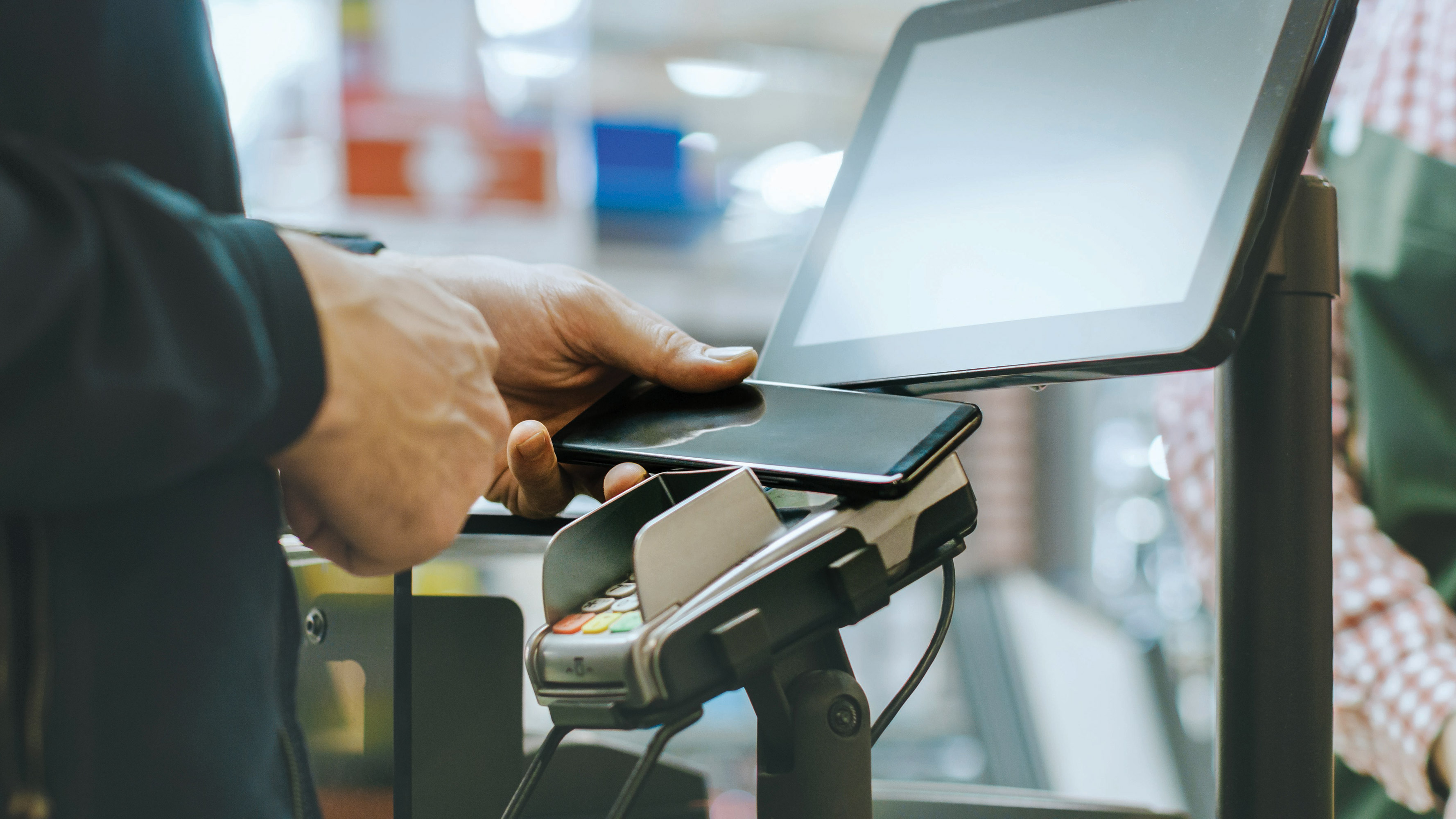 A person waves their smartphone over a credit card payment terminal to make a mobile payment at a checkout counter inside of a CVS Pharmacy store.