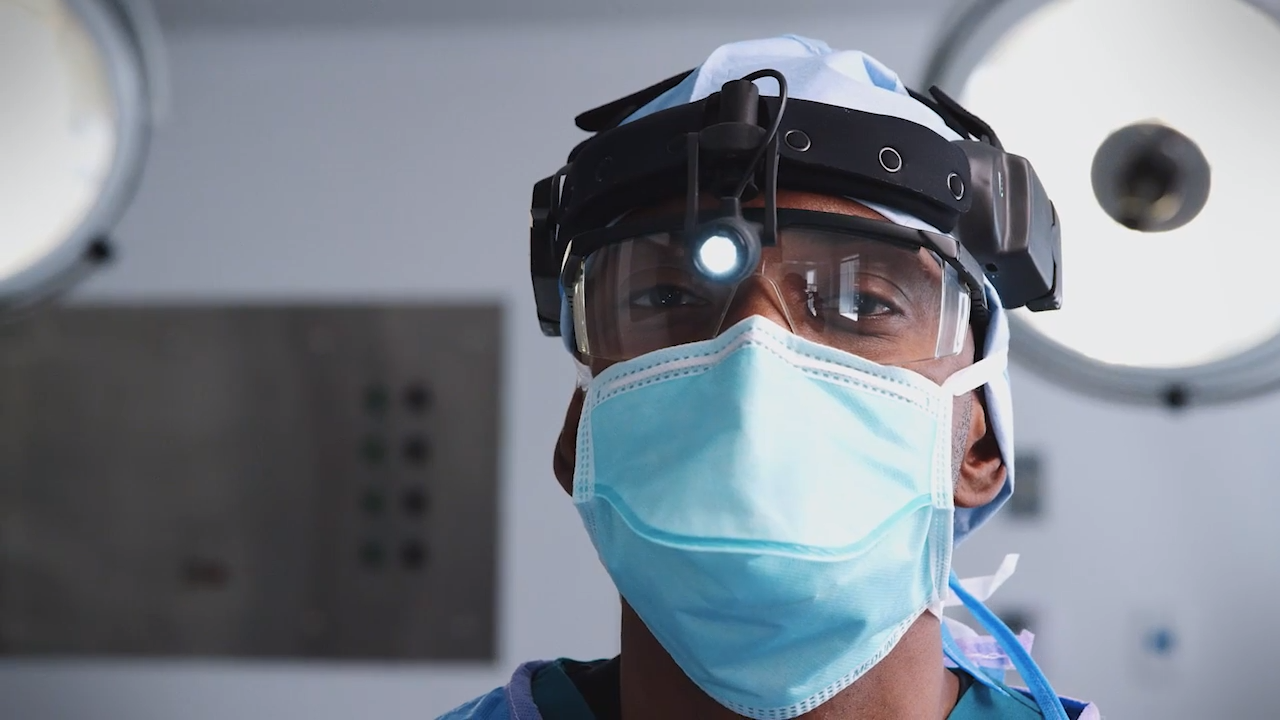 A hospital worker, wearing PPE, pauses between tasks.