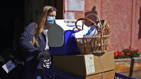 A female volunteer pushes a cart full of food donation while wearing a face mask.