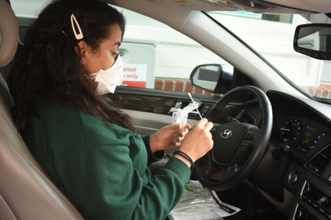 CVS patient in car prepping COVID-19 test at drive-thru testing site