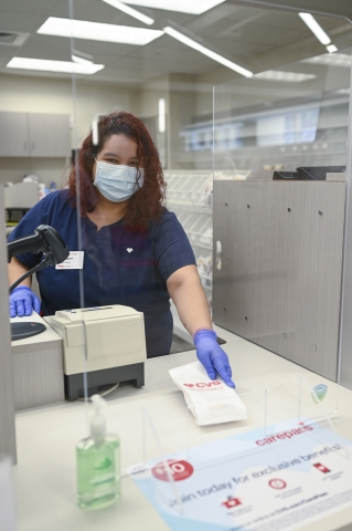 A CVS pharmacy technician prepared a prescription while wearing personal protective equipment (PPE) behind a plexiglass shield.
