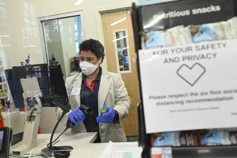 A CVS pharmacists scans a prescription while wearing personal protective equipment (PPE) behind a plexiglass shield.