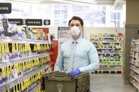 A CVS Pharmacy Store Manager, in personal protective equipment (PPE), restocks store shelves.