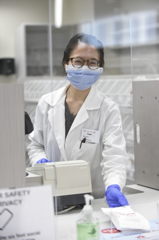 A CVS pharmacist slides a prescription under a plexiglass barrier at the pharmacy counter while wearing personal protective equipment (PPE).