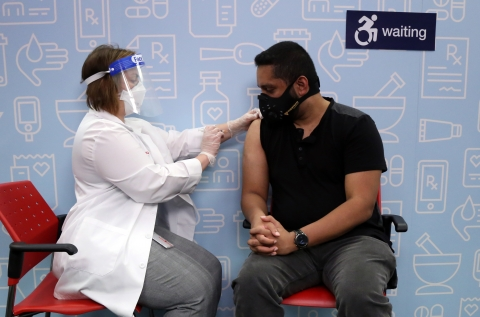 A CVS pharmacist administers a flu vaccine to a patients, both wearing personal protective equipment (PPE) and face masks.