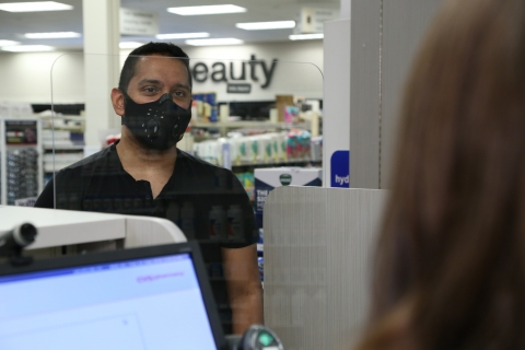 A man, wearing a face mask, checks in with a CVS Pharmacy technician in order to receive a flu vaccination.