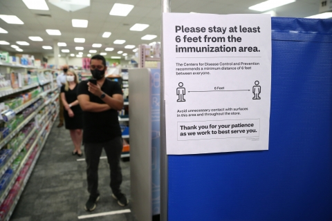 A man, wearing a face mask, consults his mobile phone while waiting in queue for a flu shot at a CVS Pharmacy location. A sign is seen in the foreground encouraging social distancing (maintaining a six-foot distance) between patients and the flu vaccination area