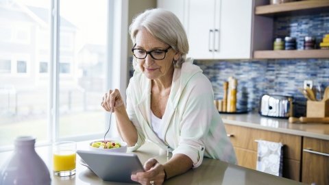 An older female with silvery, long hair eats a bowl of fruit in her kitchen while using a tablet computer to access digital health services.