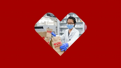 A CVS pharmacist preparing and bagging prescriptions while wearing personal protective equipment (PPE).