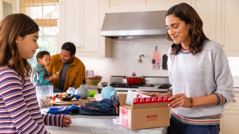 A female, surrounded by her family in their kitchen, opens a delivery box from CVS Pharmacy.