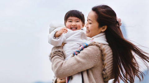 A mother, holding her infant daughter, smile and enjoy an outdoor adventure.