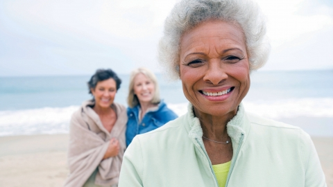 An older woman smiles while relaxing at the beach with two female friends.
