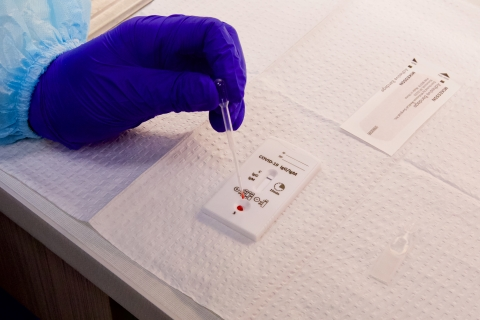 Gloved hand empties the blood from a capillary tube to a COVID-19 antibody test.