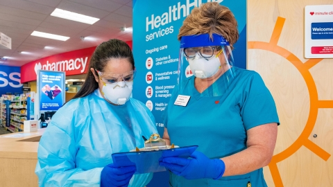 Two CVS Pharmacy technicians, wearing personal protective equipment (PPE), go over paperwork in a HealthHUB location.